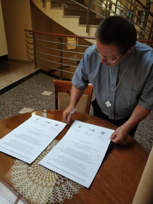Biskup G. Ryś podpisuje akt przekazania ikon